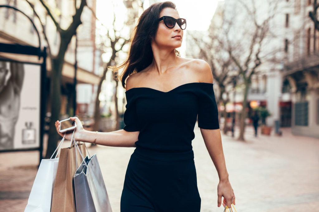 Beautiful female walking on the street with shopping bags