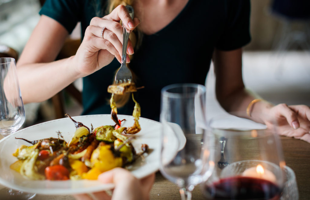 Person eating a meal at a restaurant with a glass of wine
